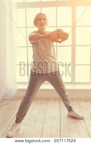 Full of enthusiasm. Full length of a nice aged woman standing near window and doing stretching exercises at home