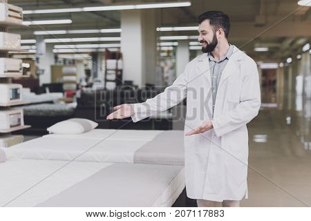 Male Orthopedic Posing Against The Background Of Mattresses And Beds And Showing A Hand On Them