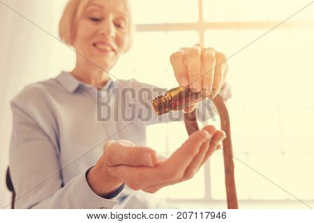 Effective pain killers. Close up of pills in hands of an aged woamaholding them and smilinghile improvinger health