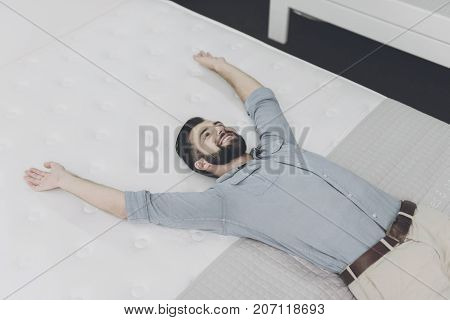 A Man Chooses A Mattress For Himself In The Store. He Is Lying On One Of Them