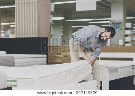 A Man Inspects A Mattress In A Mattress Store. He Lifted One Of Them