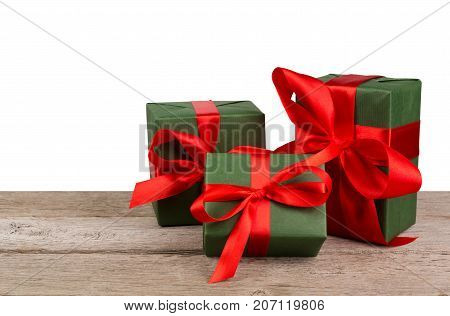 Group of gift boxes wrapped with green paper and red satin ribbon on wooden table at white background. Modern presents for any holiday, christmas, valentine or birthday