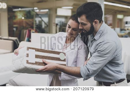 An Orthopedic Woman Shows The Man A Sample Of The Mattress He Wants To Buy