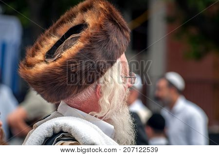 Hasid in the traditional headgear shtreimel on the street in a crowd of pilgrims. Uman Ukraine - 21 September 2017: Rosh Hashanah Jewish New Year