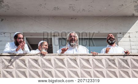 Pilgrims of Hasidi on the balcony of the high-rise building are having fun celebrating the holiday of Rosh-ha-Shana. Uman Ukraine - September 21 2017: Jewish New Year.