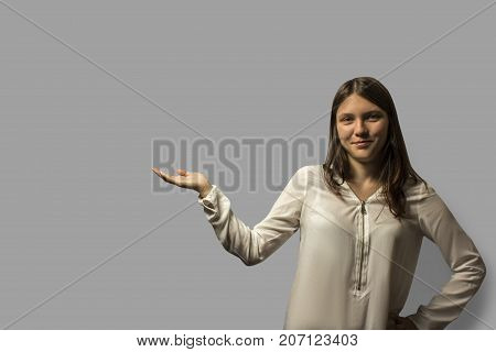 Portrait Of A Young Beautiful Student Girl With Long Hair. Holding Hand Showing Something On Open Pa