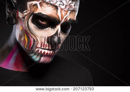 Close up portrait of man with colored skull make up. Face art, male with scary face isolated on black background.
