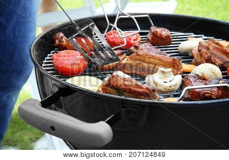 Cooking of appetizing juicy spare ribs and vegetables outdoors