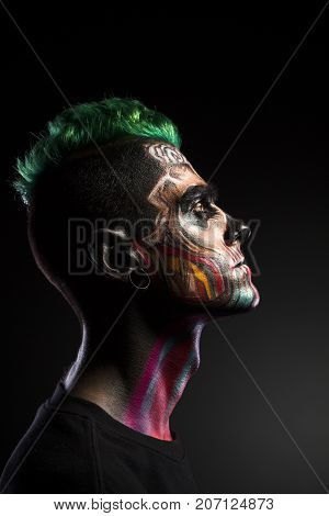 Side view of man with scary makeup isolated on black background. Face art, colored mystical makeup on mans face.