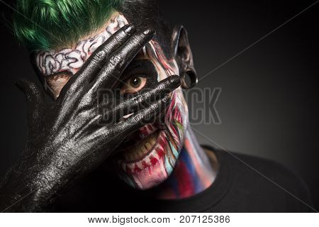 Face art, man with pro skeleton make up, covering face with black painted hand.