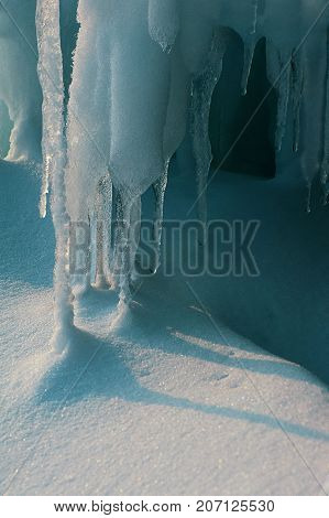 White icicles and snow are smelting under sun