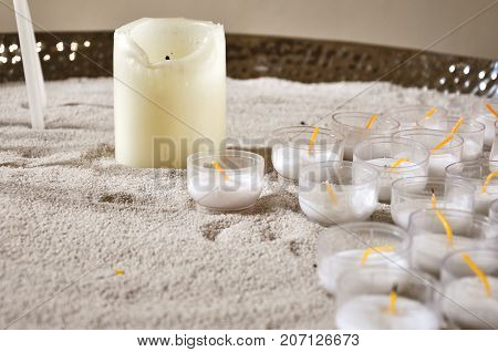 Many unlit candles on white sand close up.