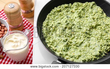 Frying pan with tasty spinach sauce on electric cooker in kitchen