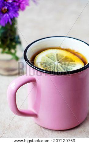 A pink mug with black tea and lemon on a light background and a glass vial with purple flowers.