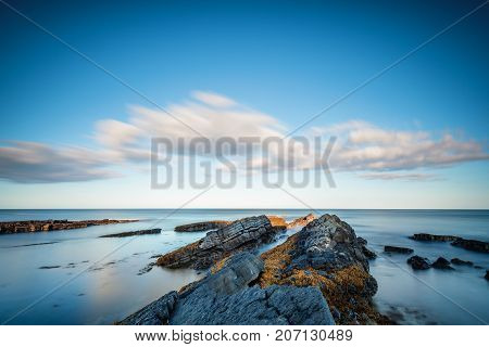 Long Exposure at Howick Coastline, the rocky shoreline on the Northumberland coasts AONB, showing motion blur of the North Sea