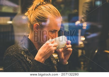 close up portrait of young beautiful female drinking latte macchiato in coffee shop