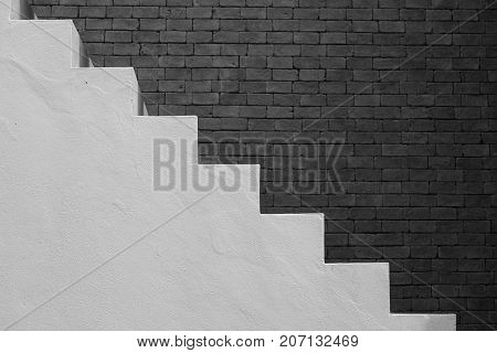 Side view of white empty stairs with brown brick wall background in vintage style. (Black and White filter effect)