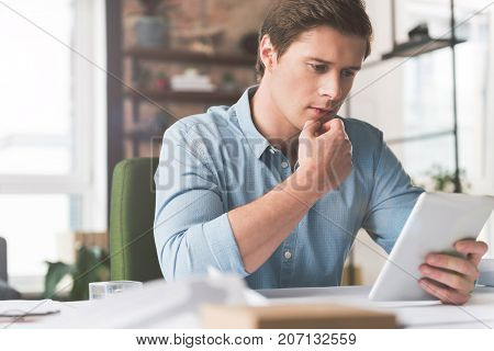 Important news. Serious young businessman is holding tablet and reading information with concentration. He is sitting at table in cozy office and touching his lips thoughtfully