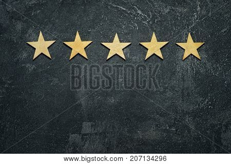 Five stars in a row on a black rustic cement boards. Conceptual of service rating and quality of trade. Top view copy space for your text.