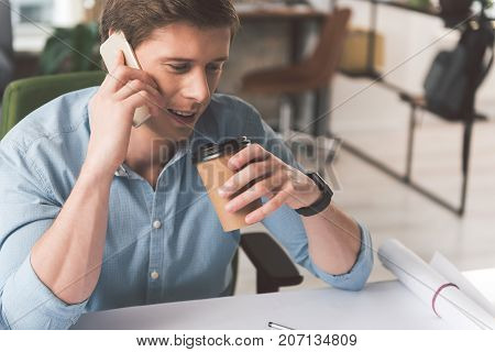 Enjoying friendly talk. Pleasant relaxed young man is drinking hot espresso while having distance dialogue on mobile phone. He is sitting at table in office and looking down thoughtfully. Copy space