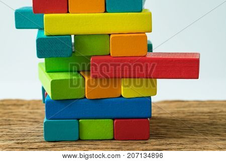 unstable colorful wooden block tower as Risk or stability concept.