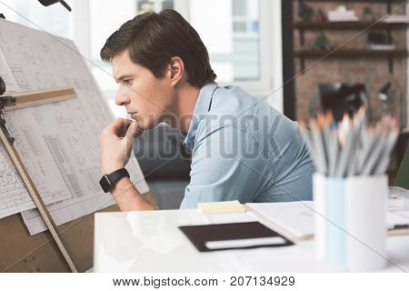Where is mistake. Profile of serious experienced young engineer is sitting near drawing board and looking at blueprints with concentration. He is touching his chin thoughtfully. Selective focus