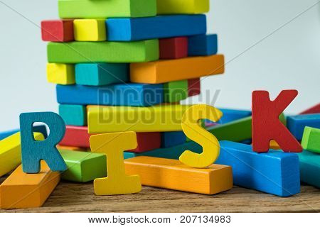 risk concept with colorful wooden alphabets RISK on collapse wooden blocks tower.
