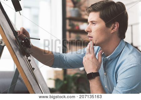 Qualified worker. Profile of professional young architect is correcting his building plan with concentration. He is sitting near drawing board and touching his chin thoughtfully
