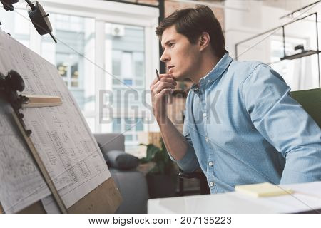 Need fresh idea. Profile of serious young attractive engineer is looking at drawing board with blueprint and touching his chin thoughtfully. Window in background
