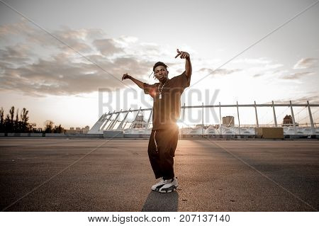 Outdoor full length portrait of the gesticulating afro american guy dressed in trendy black clothes