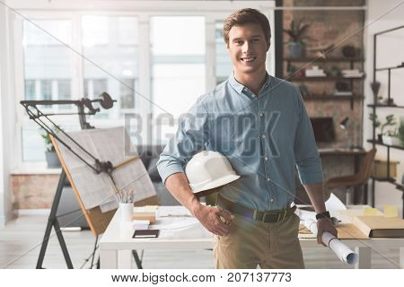 Ready to visit object. Portrait of cheerful young architect is looking at camera with joy while standing with blueprint in right hand and safety-helmet under his left arm. Copy space
