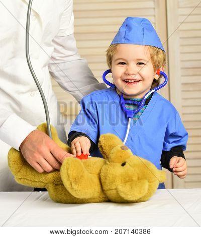 Little Assistant Examines Teddy Bear. Male Hand Holds Bear