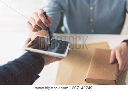 Electronic sign. Close-up of stylus in hand of guy and digital screen in hand of courier. Male is holding box and putting his signature after accepting delivery
