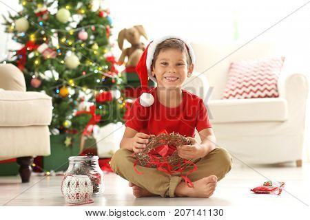 Cute boy decorating Christmas wreath on floor