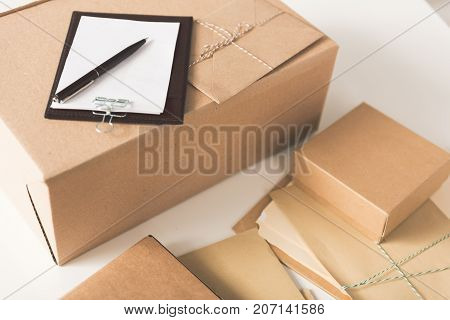 Everyday post. Close-up top view of folder with invoice, boxes and envelopes are on desk in sorting center. Copy space in the right side