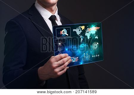 Business Technology Internet and network concept. Young businessman working on a virtual screen of the future and sees the inscription: Agenda