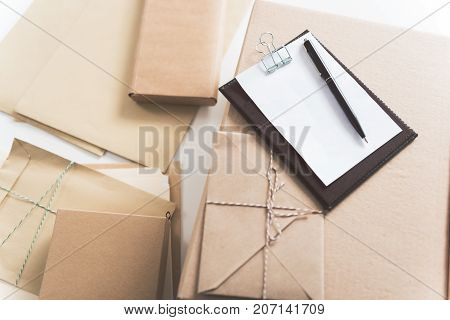 Sorting center. Close-up top view of folder with delivery note, boxes and envelopes are on table. Copy space in the left side