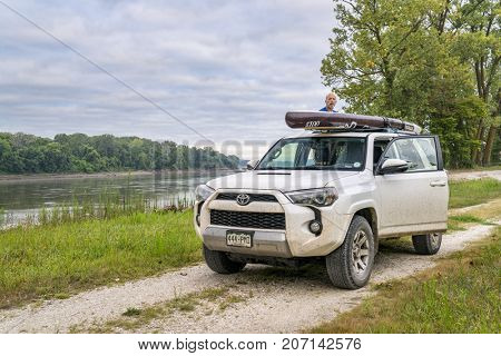 Dalton Bottom, MO, USA - August 14, 2017: Loading stand up paddleboard on a roof of Toyota 4Runner (2016 Trail Edition) SUV on a shore of the MIssouri RIver.