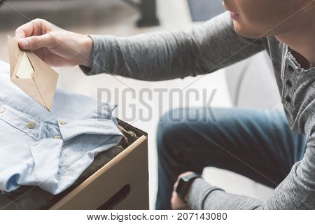 Focus on close up man hand keeping envelope. He reading it in living room near post box
