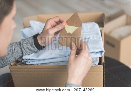 Focus on close up male arms keeping letter near package with clothes. Delivery concept