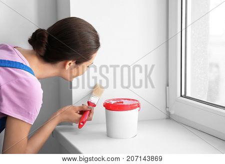 Female decorator painting wall near window indoors