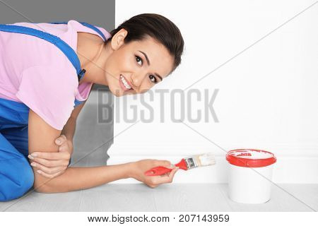 Female decorator painting wall indoors