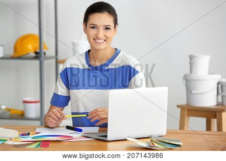 Young female decorator in office
