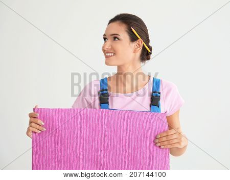 Female decorator holding color wallpaper on white background
