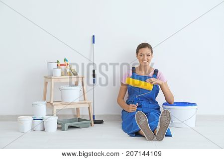 Young female decorator with paint roller resting in room