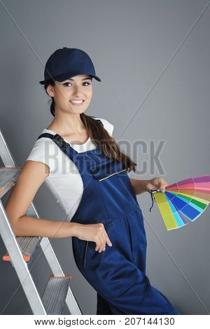 Young female decorator with color palette samples near ladder against grey background