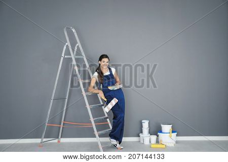 Young female decorator with paint roller and color palette samples near ladder in room