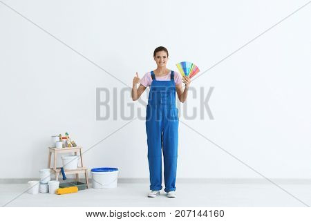 Female decorator holding color palette samples near white wall indoors