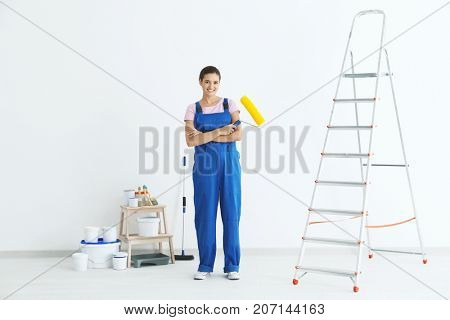 Young female decorator with paint roller near ladder in room
