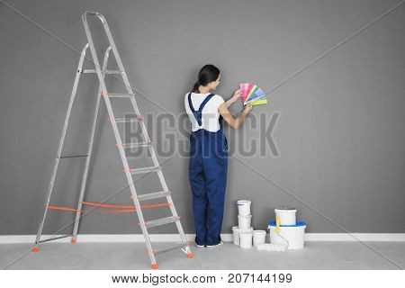 Female decorator holding color palette samples near grey wall